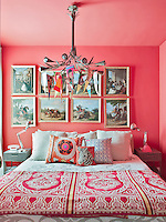 The bedroom is an eclectic and exotic mix with deep pink walls, a collection of 19th century Spanish paintings, a 20th century chandelier festooned with bunting and patterned bedding