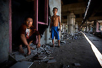 14 year old Ginanjar Salmet salvages reusable building materials with his 11 year old brother Atha Barokah from an abandoned building under the elevated highway in North Jakarta. Both the children study at the 'Twin Teachers'' Kartini Emergency School. Since the early 1990s, twin sisters Sri Rosyati (known as Rossy) and Sri Irianingsih (known as Rian) have used their family inheritance to set up and run 64 schools in different parts of Indonesia, providing primary education combined with practical skills to some of the country's most deprived children...
