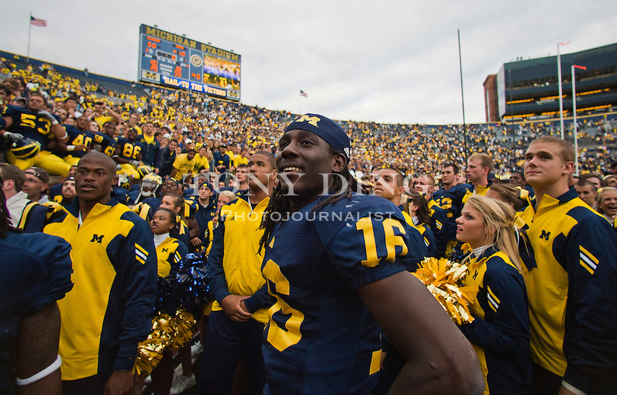 Michigan quarterback Denard Robinson (16) smiles at fans as he celebrates with teammates after an NCAA college football game with with Connecticut, Saturday, Sept. 4, 2010, in Ann Arbor. Michigan won 30-10. (AP Photo/Tony Ding)