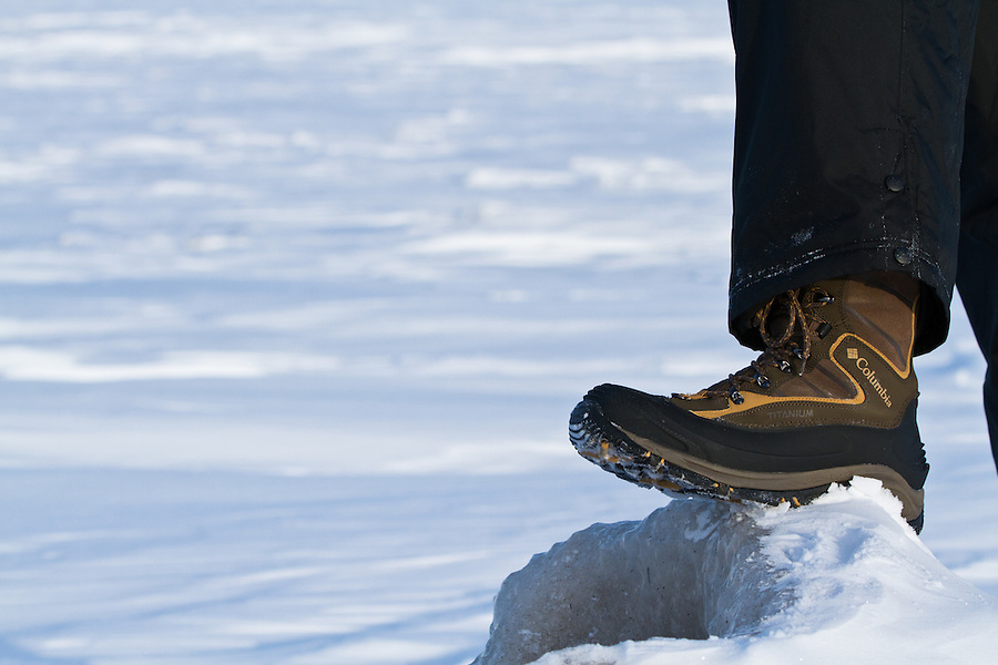 A man wearing Columbia Boots perches his foot on a large chunk of ice.