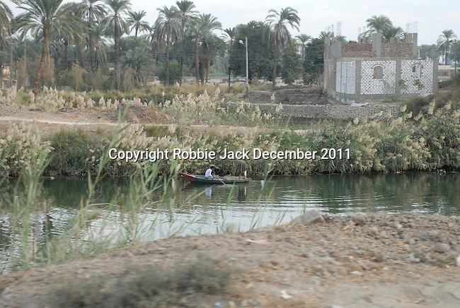 People fishing in a canal on the West Bank near Luxor.The town of Luxor occupies the eastern part of a great city of antiquity which the ancient Egytians called Waset and the Greeks named Thebes.
