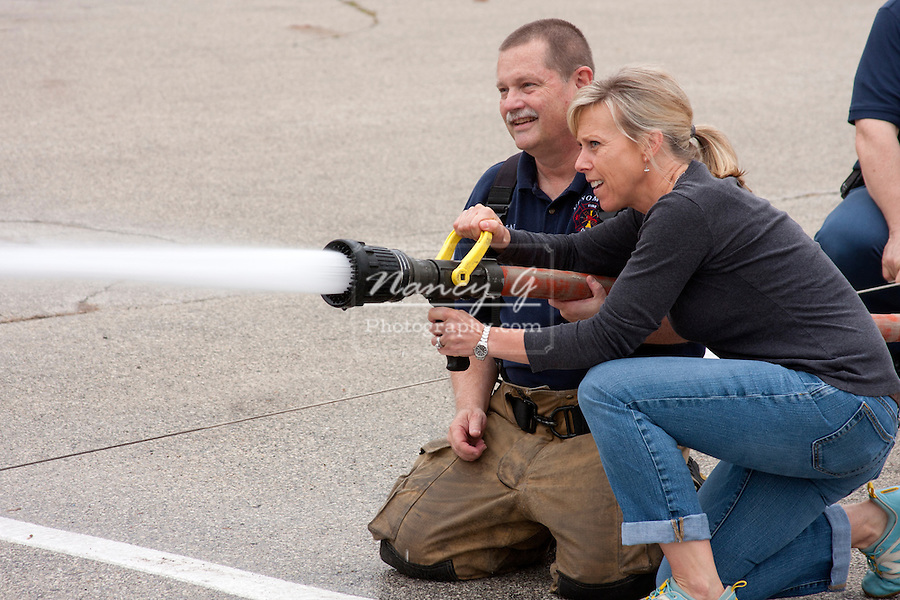 A woman using a fire hose to spray water with a firefighter in Menomonee Falls Wisconsin
