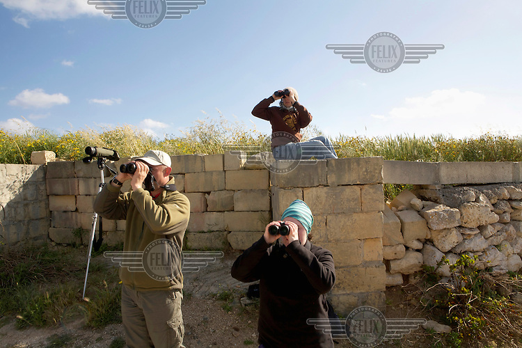 A team of three volunteer monitors scans the skies for migrating birds and illegal hunters targeting them. Under EU leglislation, hunting or trapping birds in spring is illegal but the government of Malta, which joined the EU in 2004, allows hunting of turtle dove and quail at this time of year. Some 170 species of bird pass over Malta during the spring and autumn migration periods. Hunters regularly shoot other species including birds of prey which are stuffed for private collection. Spring Watch Malta is a conservation camp run by BirdLife Malta, a non-profit which lobbies against bird hunting in the country. In 2012, fifty volunteers from across Europe converged on a tourist hotel in Bugibba in northern Malta and fanned out to track migrating birds and monitor any illegal spring hunting by the 11,000 permitted hunters...