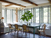The kitchen/dining area has a custom-made banquette around a dining table of reclaimed wood
