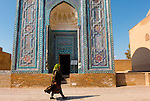 Uzbek woman passing by a timurid-era mausoleum at Shahi Zinda Necropolis, Samarkand