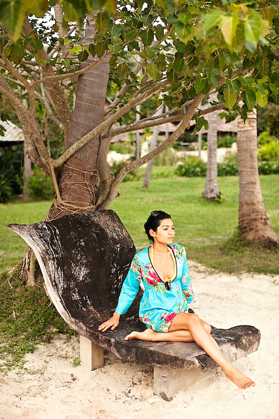 Woman Reading on Lounge Chair at Kamalaya, Koh Samui, Thailand. A woman reads a book on a wooden lounge chair by Ao Thai beach at Kamalaya resort.