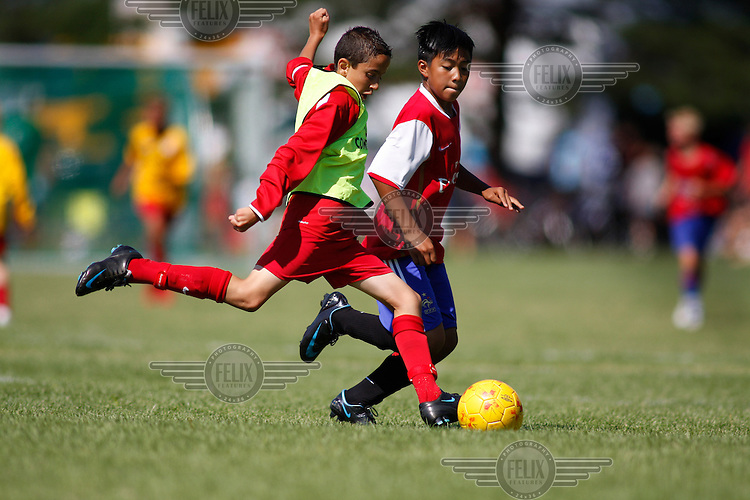 A player from Norwegian team Holmlia (left) being chased a player from team RIFA of the Philippines. Norway Cup is the worlds largest football tournament, in 2008 bringing together 30.000 children from all over the world, aged 10 to 19. They make up 1386 teams playing a total of 4400 matches during the week they play. The tournament is played on a big grass field just outside the center of Oslo, Norway.