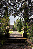 A gravel pathway leads up to the castle through the picturesque gardens