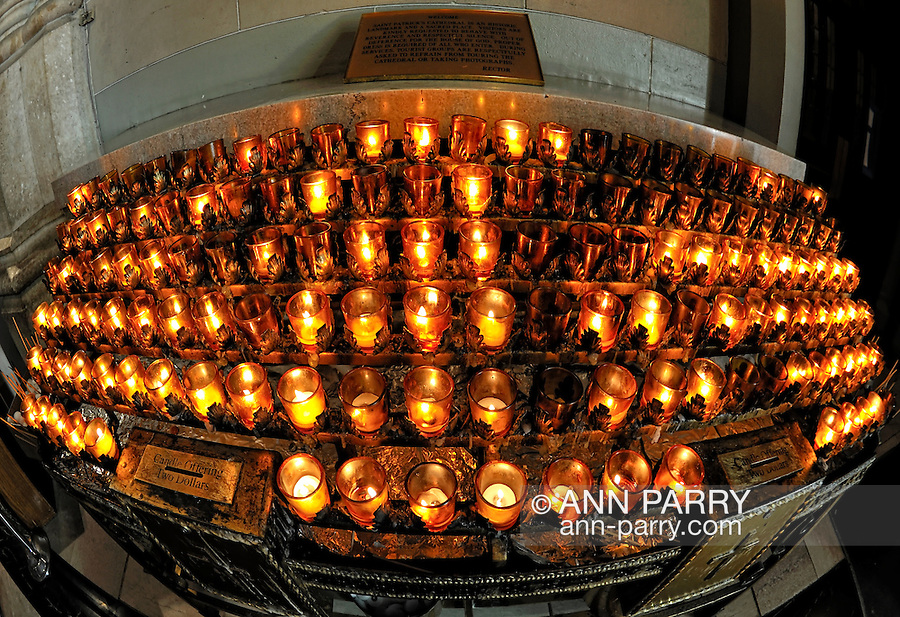 Votive candles at St. Patrick's Cathedral, with sign above asking visitors to dress proprely and not take photos during mass services. 180 degree fisheye lens view, NYC, 2011