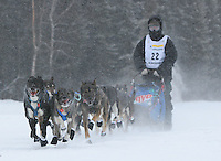 Saturday February 25, 2006 Willow, Alaska.  Rohn Buser  runs down the trail on Willow Lake at the start day of the Junior Iditarod sled dog race.  Willow Lake.