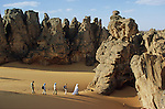 We ramble in this rocks forest, fascinated by the phantasmagorical shapes, sculpted and destroyed by wind, sand and water. We follow a sandy crest until we strike against a bronze sandstone wall.  Tassili of Maghidet