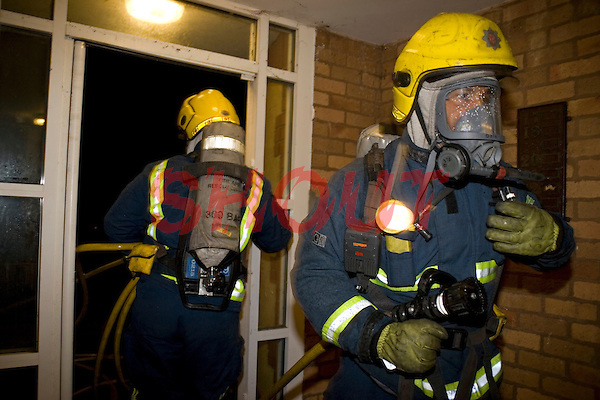 Firefighters wearing BA and carrying an hose reel enter block of flats. This image may only be used to portray the subject in a positive manner..©shoutpictures.com..john@shoutpictures.com