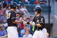 Josh Phegley (4) of the Charlotte Knights bumps fists with teammate Jordan Danks (20) after hitting a home run against the Scranton/Wilkes-Barre RailRiders at BB&T Ballpark on July 17, 2014 in Charlotte, North Carolina.  The Knights defeated the RailRiders 9-5.  (Brian Westerholt/Four Seam Images)
