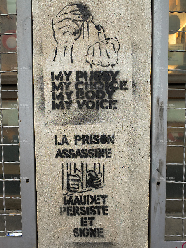"Switzerland. Geneva. Graffiti on the wall. A person has writen the words: My pussy. My choice. My body. My voice. The graffiti contains explicit language and sexual references. Sexually explicit language. In Western culture, the finger (as in giving someone the finger or the bird, also known as the finger wave, the middle finger, flipping someone off, flipping the bird, shooting the bird, the rude finger, the one finger salute) is an obscene hand gesture. It communicates moderate to extreme contempt, and is roughly equivalent in meaning to ""fuck off"", ""fuck you"", ""shove it up your ass"", ""up yours"" or ""go fuck yourself."" It is performed by showing the back of a closed fist that has only the middle finger extended upwards, though in some locales the thumb is extended. Extending the finger is considered a symbol of contempt in several cultures, especially Western cultures. The second drawing shows two hands on prison's bars and the text says. Prison is killing people. Maudet signs and oerseveres. Pierre Maudet is a Swiss politician, a member of FDP and a Member of the Conseil d'Etat in charge of the Department of the Security and the Economy (DSE). 12.02.2014 © 2014 Didier Ruef"