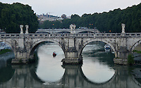 Michael McCollum.6/24/11.A bridge over the Tiber river in Rome at dusk.