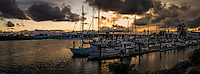 Boats, moored at the Aeolian Yacht club under glowing sunset clouds and the Bay Island Bridge between in Alameda, California.  Panoramic combination of multiple images.