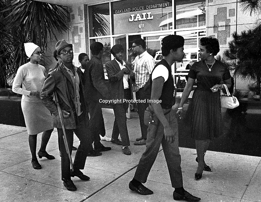 Black Panthers including Bobby Hutton (with shotgun) Bobby Seale and other armed Panthers in front of the Oakland Police Dept. Jail. (1967 photo by Ron Riesterer)