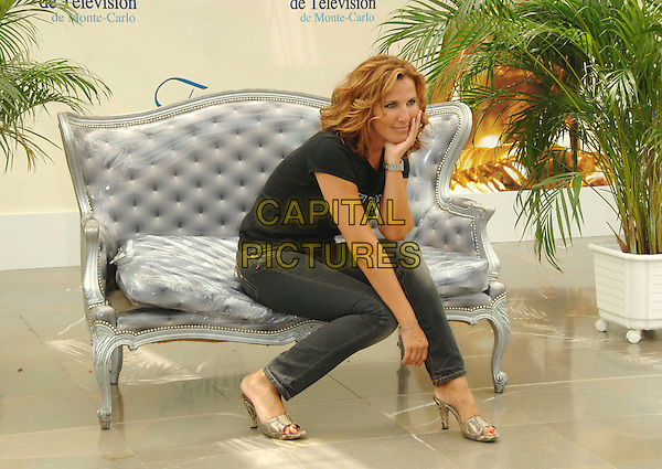 "NATACHA AMAL .attends a photocall promoting the television series ""Femmes de Loi"" on the fifth day of the 2008 Monte Carlo Television Festival held at Grimaldi Forum, in Monte Carlo, Principality of Monaco, June 12, 2008. .full length new york top slogan black jeans sitting arm.CAP/TTL .©TTL/Capital Pictures"