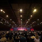 A huge crowd watches a motivational speaker at the Excel international conference and event arena, London