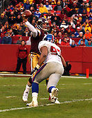 Landover, MD - December 8, 2002 -- Washington Redskins rookie quarterback Patrick Ramsey (11) releases the ball just as New York Giants defensive tackle Cornelius Griffin (97) is about to hit him in fourth quarter action in Landover, Maryland.  The Giants won the game 27 - 21..Credit: Ron Sachs / CNP.[NOTE: No New York Metro or other Newspapers within a 75 mile radius of New York City]