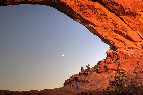 Photographers shoot the moon from within the North Window at Arches National Park, Utah