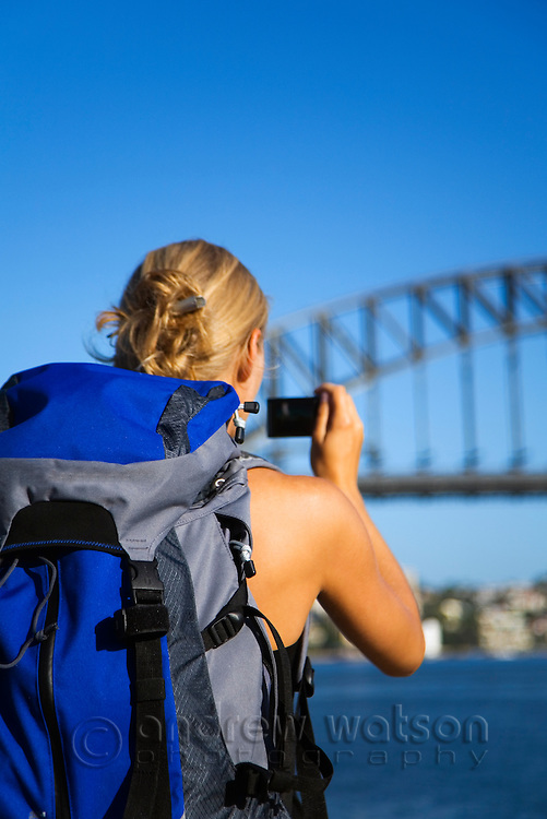 A backpacker photographs the Sydney Harbour Bridge.  Sydney, New South Wales, AUSTRALIA.