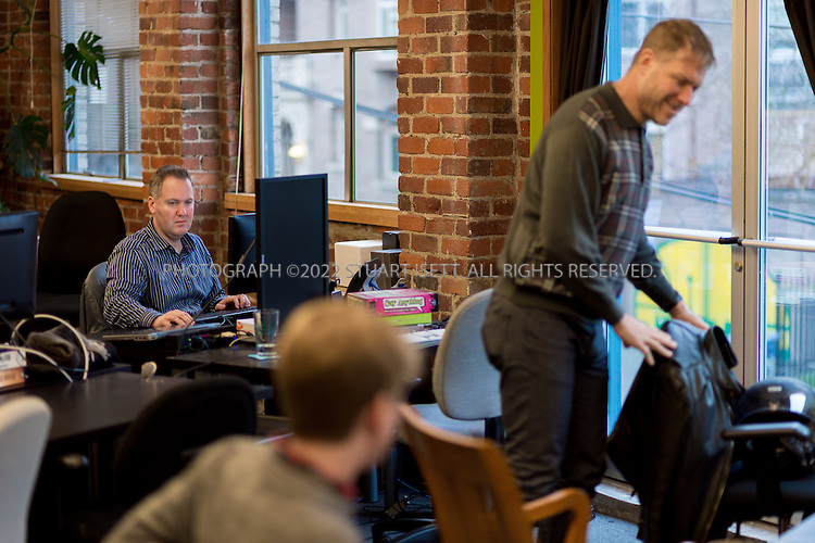2/28/2014&mdash;Seattle, WA, USA<br /> <br /> Chris Hammersley, 42 (back left), a Seattle based e-commerce executive, working at his desk at Office Nomads, a coworking space in Seattle&rsquo;s Capitol Hill neighborhood. Hammersley is based in Seattle, but his company HQ is in Walnut Creek, Ca. and his bosses live in Chicago and Boston. When meetings take place, they can happen anywhere, so Chris uses coworking spaces in those cities and others when he travels for work. <br /> <br /> <br /> Photograph by Stuart Isett. <br /> &copy;2013 Stuart Isett. All rights reserved.