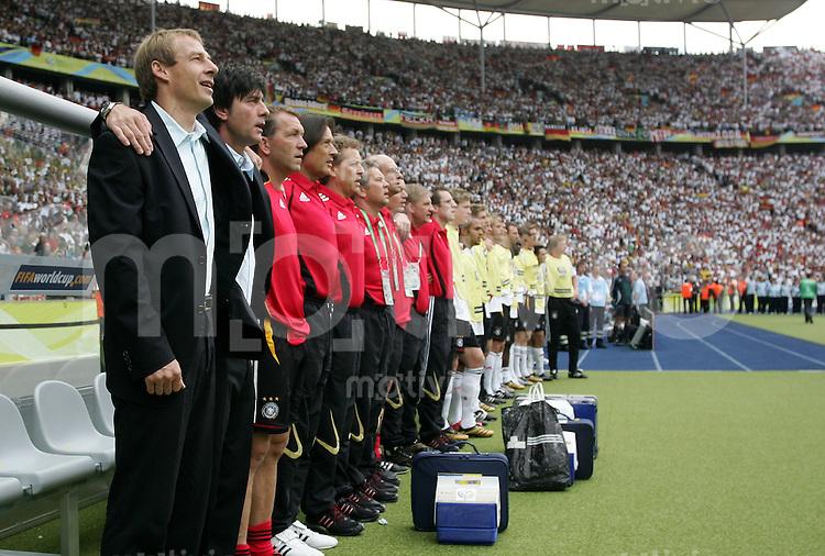 Fussball WM 2006 Viertelfinale in Berlin, Deutschland - Argentinien Bundestrainer Juergen Klinsmann (li.), Co-Trainer Joachim Loew und die Mannschaft halten sich in den Armen waehrend der Nationalhymne.