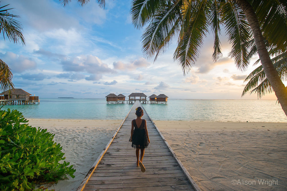 Maldives, Rangali Island. Conrad Hilton Resort. Little girl walking down the boardwalk to the spa at sunset.