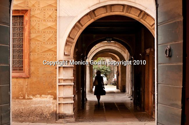 Street scene in Como, Italy a city on Lake Como..A woman walks through an archway in Como, Italy.