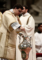 Un diacono versa olio santo in un'anfora durante la Santa Messa del Crisma celebrata dal Papa nella Basilica di San Pietro, Citta' del Vaticano, 13 aprile 2015.<br /> A deacon pours holy oil inside an amphora during a Chrism Mass celebrated by the Pope in St. Peter's Basilica at the Vatican,at the Vatican, on April 13, 2017.<br /> UPDATE IMAGES PRESS/Isabella Bonotto<br /> STRICTLY ONLY FOR EDITORIAL USE