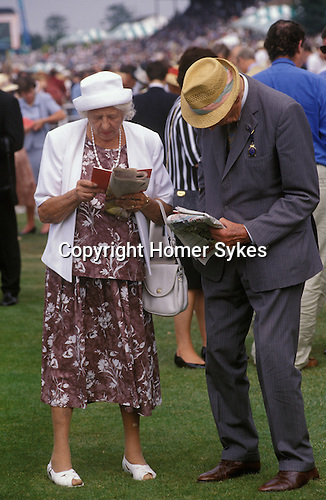 Elderly couple looking at their race cards at Glourious Goodwood. Surrey