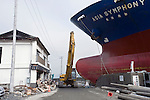 A crane is driven past a cargo ship, the 6175 dwt Asia Symphony, that has crashed into the sea wall after being swept inland by the March 11 tsunamis at the historic city of Kamaishi, Iwate Prefecture, Japan on 11 June, 2011, exactly 3 months after the disasters. Photographer: Robert Gilhooly