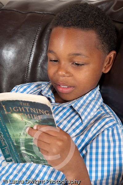 clsoeup of 8 year old boy reading fiction book on couch vertical