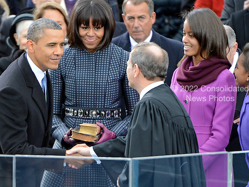 United States President Barack Obama shakes hands with U.S. Chief Justice John Roberts after taking the oath of office during the public swearing-in ceremony at the U.S. Capitol in Washington, D.C. on Monday, January 21, 2013.  From left to right: President Obama, first lady Michelle Obama, U.S. House Speaker John Boehner (Republican of Ohio), Malia Obama, and Sasha Obama..Credit: Ron Sachs / CNP.(RESTRICTION: NO New York or New Jersey Newspapers or newspapers within a 75 mile radius of New York City)
