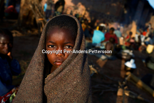 DUBIE, DEMOCRATIC REPUBLIC OF CONGO DECEMBER 11: An unidentified girl takes shelter under a blanket as she is one of thousands of newly arrived refugees who gathered outside a military base on December 11, 2005 in Dubie, Katanga Province in Congo, DRC. They have been fleeing fighting between the Congolese army and Mai-Mai rebels in Eastern Congo. They are some of the victims of the civil war that started in 1996. Many people have moved from area to area the last years trying to find safety. About four million people have died in Congo since 1996, making it the deadliest humanitarian crisis in recent memory. Most of people have died of preventable diseases such as malaria, measles, diarrhea, respiratory infections and malnutrition. The health system has collapsed and very few people have access to healthcare. Congo is planning to hold general elections by June 2006, the first democratic elections in forty years..(Photo by Per-Anders Pettersson/Getty Images)...