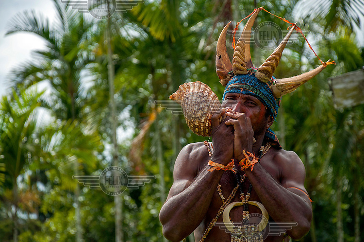 A member of the Vijari Jajora tribe blows on a conch shell during an evacuation drill (a signal used in case of disaster).