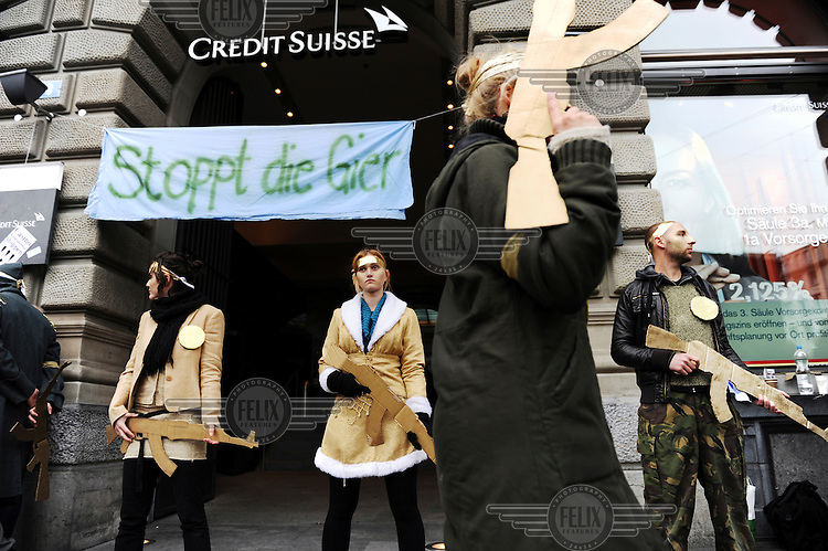 Occupy movement on Paradeplatz, centre of the Swiss banking industry, on a day of action with people dressed in gold, including face paint, and cardboard weapons in front of the headquarters of Credit Suisse, with a banner slogan 'Stoppt die Gier' .