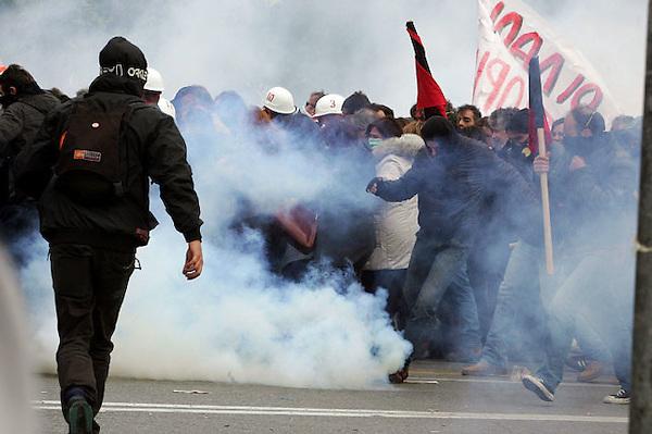 ARA08. ATENAS (GRECIA), 23/02/2011.- Policía antidisturbios ganzan gases lacrimógenos a protestantes durante los enfrentamientos entre grupos de radicales y las fuerzas de orden ocurridos en la manifestación convocada con motivo de la huelga general contra la rígida política de ahorro del Gobierno, en el centro de Atenas, Grecia, el 23 de febrero de 2011. EFE/Simela Pantzartzi