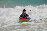 A boy rides a wave using a bodyboard at Kailua Beach, Oahu, Hawaii.