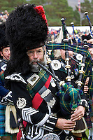Bagpipe player of massed band of Scottish pipers at Braemar Games Highland Gathering, Scotland