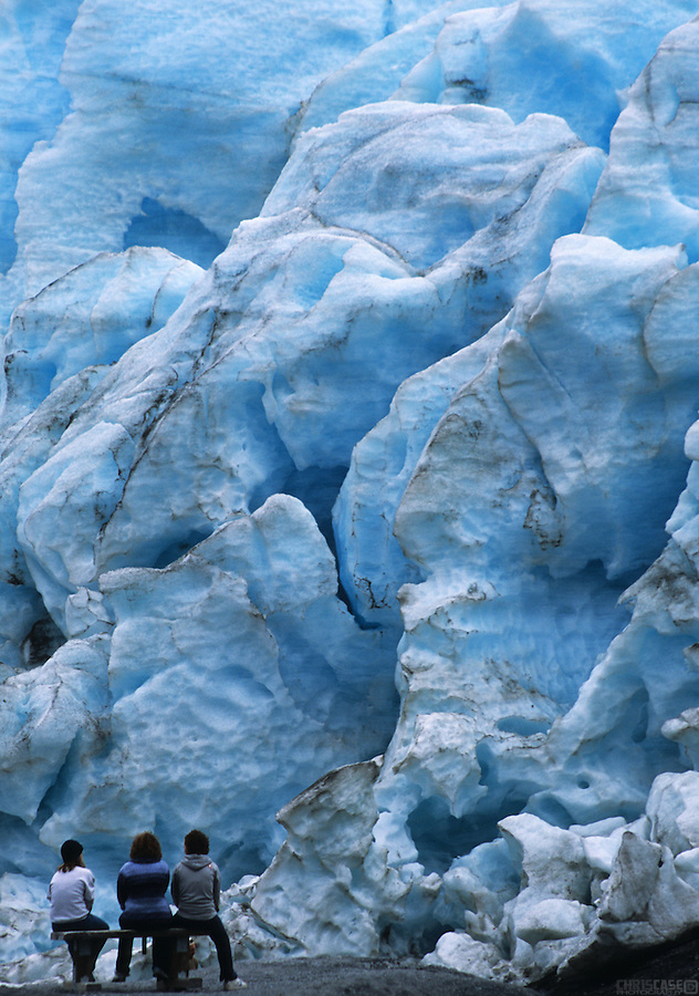 Three visitors are dwarfed by the looming glaciers of Kenai Fjords National Park, Alaska.