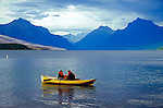 Tourists paddle a boat on placid Lake McDonald on a cloudy summer day in Glacier National Park in Montana USA