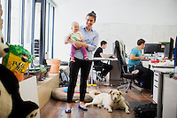Dulcie Madden, co-founder and CEO of Mimo, holds 10-month-old Sadie Gutner at the Mimo headquarters Boston, Massachusetts, USA, on Mon., April 28, 2014. Sadie is the daughter of Mike Gutner who handles operations for Mimo, and she is wearing one of the company's onesies, made by Mimo, which has a variety of sensors on it. The onesie has a detachable frog-shaped communication device that transmits data from the onesie's sensors and sends the data to a smartphone app, which displays information about the baby's respiration, skin temperature, position, and activity level. The onesie is washable and the device is water-resistant.