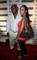 MIKE TYSON & LAKIHA SPICER.The Ante Up for Africa Celebrity Poker Tournament at the Rio Resort Hotel and Casino, Las Vegas, Nevada, USA..July 2nd, 2009.full length married husband wife white shirt brown bag purse pink strapless top looking over shoulder tattoo .CAP/ADM/MJT.© MJT/AdMedia/Capital Pictures