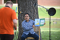 Toby McDonald (left), technician with the Springdale Public Library, videos Monday, July 27, 2020, pastor Billy Tatios, with the New Hope Marshallese Church, read during the Springdale Public Library's Marshallese Story Time in Murphy Park in Springdale. The story time, organized by Tanya Evans, multicultural outreach librarian, features guest Marshallese community members to read in the native language. The library is closed temporarily because of the the covid-19 pandemic but still offers many services including the online programming, a virtual summer reading program and curbside pick up. Check out nwaonline.com/200728Daily/ and nwadg.com/photos for a photo gallery.<br /> (NWA Democrat-Gazette/David Gottschalk)