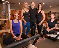 From left, student Barbara Williams, instructor Beth Butterworth, owner/instructor Mike Zelesko, studio director/instructor Sue Long and student Sally Trachy pose for a photo before a class at Transform Pilates Friday August 14, 2015 in Furlong, Pennsylvania. (Photo by William Thomas Cain)