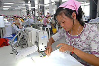 Young female workers on production lines in a textile factory in Yixing city, in the Jiangsu Special Development Zone that makes clothes for western companies including Umbro Sports and New Balance.  Much of the world's textile manufacture has moved to China due to relatively low labor rates and high productivity and those clothes are almost exclusively made by women between 6 and 25 years old..23 Sep 2006.