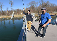 NWA Democrat-Gazette/FLIP PUTTHOFF <br /> Moji Abolhassani swings a trout toward the net held by Pasha Maleknia on Dec. 22 2018 at Lake Springdale.