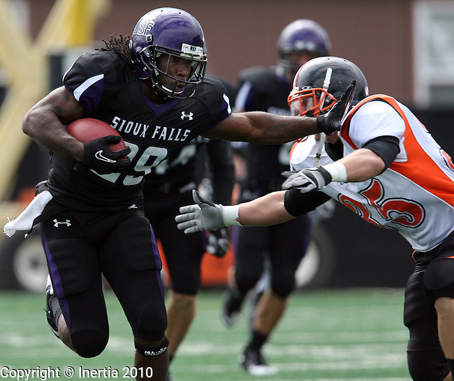 SIOUX FALLS, SD - SEPTEMBER 18: Chevon Walker #29 of the University of Sioux Falls gives Lance Snifflet #35 of Doane College a stiff-arm for a big gain in the first quarter of their game Saturday afternoon at the University of Sioux Falls/Sanford Sports Complex. (photo by Dave Eggen/Inertia)